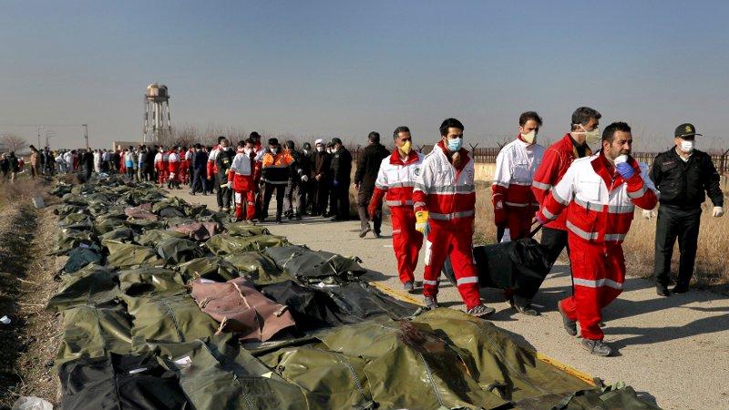 Iranske redningsmannskaper håndterer de omkomne etter flystyrten i Iran onsdag.