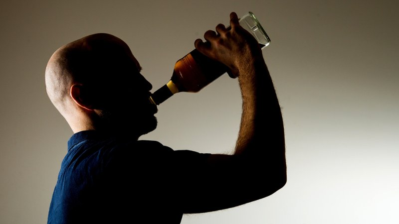 En mann som drikker fra en whiskyflaske.