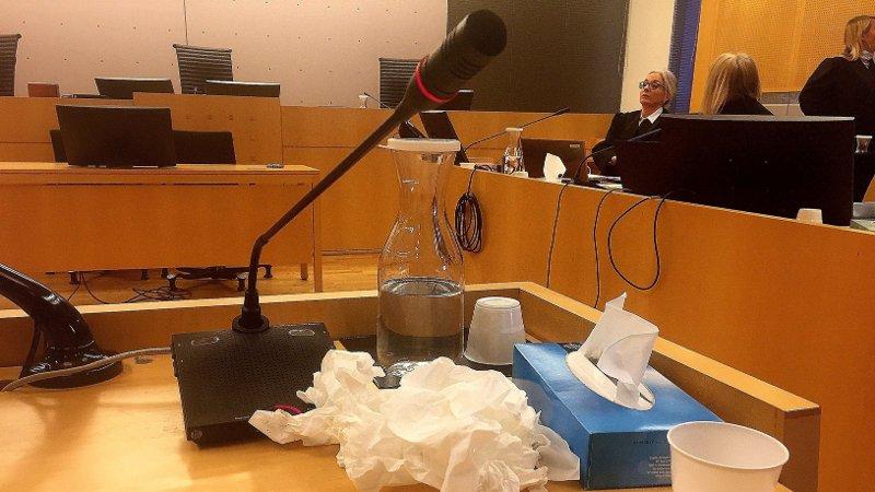 Bilde av bordet i vitneboksen, flere brukte servietter ligger på bordet, sammen med en flaske med vann og en eske med Kleenex.