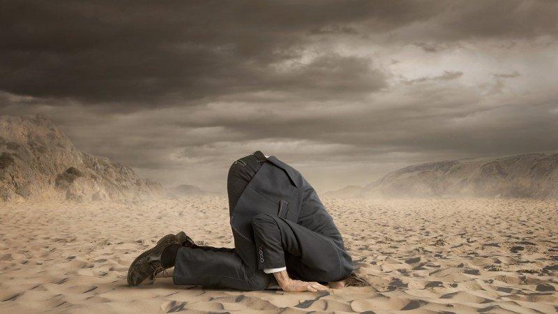Mann stikker hodet i sanden.