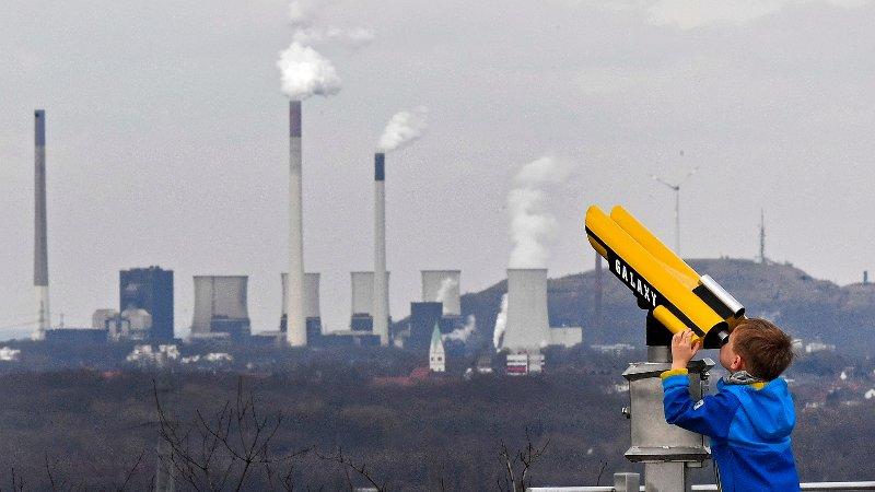 En gutt ser i kikkert mot et kullkraftverk i Gelsenkirchen i Tyskland.