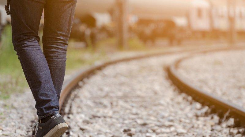 Ung mann går på togskinner.