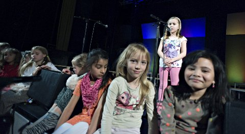 FARGESPILL: Ca 70 barn og unge fra Ås skal på scenen i Fargespill, en forestilling med musikk og sang fra mange land. Her øver Charlotte (ved mikrofonen), Faye (f.h.), Cornelia, Mina, Hjørdis, Amalia, Gudrun og Oda.  FOTO: Ole Kr. Trana