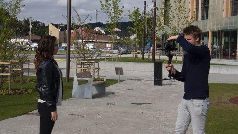 Eirik Sauarlia i sving bak kamera, mens Solveig Hartviksen poserer foran, med Bok & Blueshuset som en fin ramme rundt.