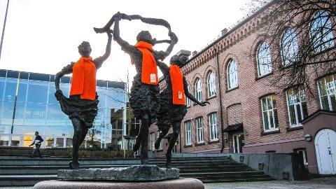 For å skape blest rundt aksjonen var oransje skjerf plassert sentralt i byen, som her på jentene i fontenen utenfor Kirkeparken videregående.