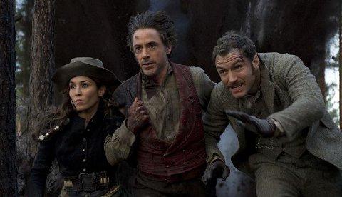 TRIO PÅ FLUKTSigøynerkvinnen Sigma, Sherlock Holmes og Dr. Watson må flykte gjennom skogen i en av scenene der det dundrer og smeller i store og små våpen. Foto: FILMWEB.NO