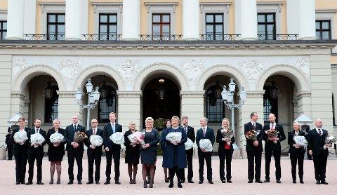 Siv Jensen og Erna Solberg står foran den nye regjeringen på Slottsplassen i Oslo etter ekstraordinært statsråd onsdag. Anne Grethe Erlandsen, er oppnevnt til ny statssekretær i Helse- og omsorgsdepartementet.