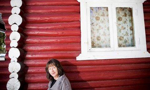 Hilde Diesen lener seg til hytteveggen på «Parkert», hennes eget navn på nabohytta til Landfallhytta. Forfatteren ble gledelig overrasket da hun ble nominert til årets Brakepris. I boka «Hytteskogen» ble teksten enda viktigere for forfatteren enn bildene. Som en følge av det er 60-åringen nå i gang med en roman– som kommer når den kommer. Foto: Ingrid Aas