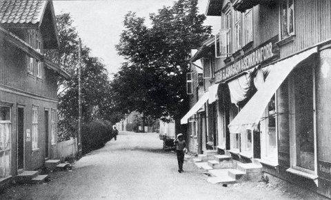 Fra byens foretningsstrøk i 1920. Huset til venstre ble etter et branntilløp flyttet til Ullerud Gård der det ble våningshus.