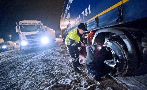 SLAPP KJØREFORBUD: Kontrollør Magne Dahle fra Statens vegvesen sjekker om en utenlandsk vogntogsjåfør klarer å sette på kjettingene sine. Dahle sier sjåføren hadde med seg en spesiell type kjettinger.