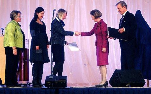 Dronning Sonja delte ut prisen til rektor Bente  Lis Larsen, elevrådsleder Ina Marie Guttulsrød og utdanningsleder Gerd Louise Molvig. Bak: Juryformannen, professor dr. philos Edvard Befring.