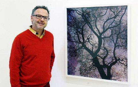 Marius Schultz foran utstillingens hovedbilde. – Treet gir meg nesten en skapelsesfølelse. Det ser ut som et nervesystem, som universet. Og sånn kan man lage sin egen historie av bildet, sier han.