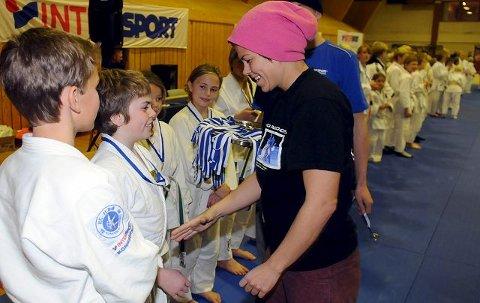 FIKK GULL: BK-gutten Brynjar Kvamme Sandvik mottar en velfortjent gullmedalje av tidligere kongepokalvinner i judo, Birgitte Ursin, under 830-cup i Kongsberghallen lørdag. FOTO: OLE JOHN HOSTVEDT