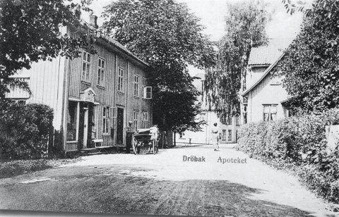 Nordover i dagens Niels Carlsens gate, som var Drøbaks første storgate. Til venstre i gaten ser vi Apoteket som opprinnelig ble bygget som allmueskole i 1816 og skjenket byen av Niels Carlsen.