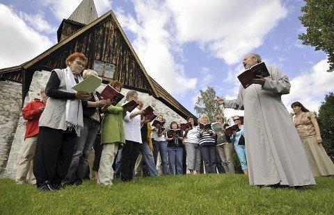 Olsok med ny vri. Søndag øvde koret med komponist og musiker Trond H.F. Kverno (t.h.) utenfor Fiskum gamle kirke. Med middelalder og historiske toner blir olsok i år feiret på en nyskapende måte. Foto: Ola Niemann