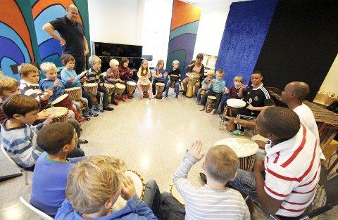 INNSATS: De tre sørafrikanerne fikk god kontakt med de unge trommeslagerne, her fra første og tredje trinn ved Åsgård skole.    FOTO: STIG PERSSON