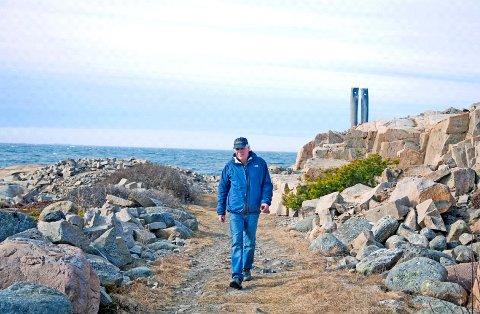 """Vegard Hanve viser rundt i skulpturparken på Røsshue, Kirkeøy, Hvaler. Bak sees unstverket """"Fortidens Vitner"""" av Alessandro Stenico"""