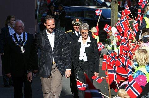 Kronprins Haakon, her flankert av fylkesmann Anne Enger og Mosseordfører Paul-Erik Krogsvold, ble ønsket velkommen til Moss av barnehagebarn med norske flagg.