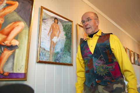 Knut Aasheim er godt fornøyd med maleriet av Marit Bjørgen. Det pryder plakaten for utstillinga som åpner lørdag. Der henger hun ved siden av ordføreren og andre «folk på Bygda» i Trysil. (Foto: Ingrid Nylund)