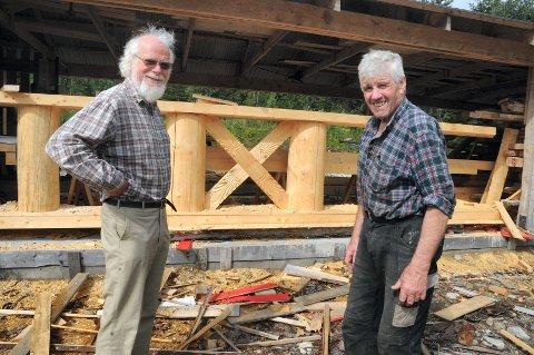 OMFATTENDE JOBB: Sigmund Bø t.v. er glad for at Odd Egil Moen (71) har tatt på seg jobben med å bygge stavkirke på Lia. Her står de ved en sentral konstruksjon i taket kirkerommet. (Foto: Tore Sandberg)