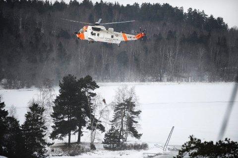 Her blir redningsmannen firt ned fra helikopteret for å hente opp personen som hadde gått gjennom isen.