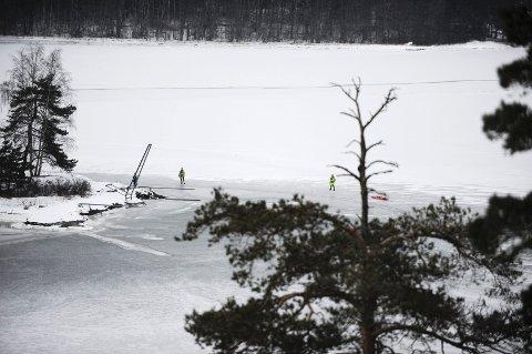 Her står brannmannskapet på isen etter at aksjonen er over. Ytterst på holmen står isfiskeren som reddet personen opp av vannet.