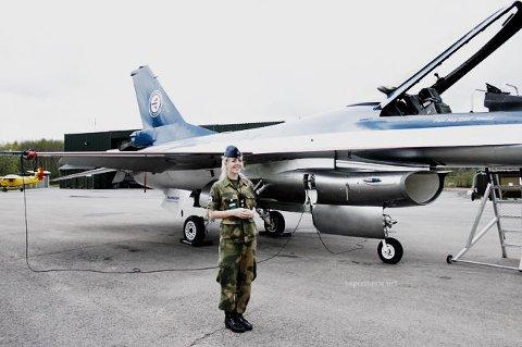 Her står Marie Brudevold foran F16-flyet hun selv har bestemt utseendet på.