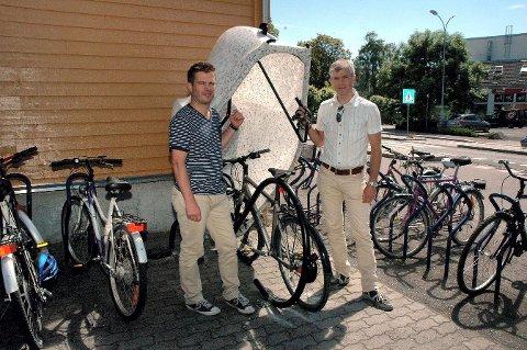 Boksen legges over sykkelen, og vips har du en liten garasje til den. Arealplanlegger Ivar Holt (til venstre) og Ole Jakob Hansen i kommunen håper syklister vil bruke den.  Foto: Jan Eric Møller