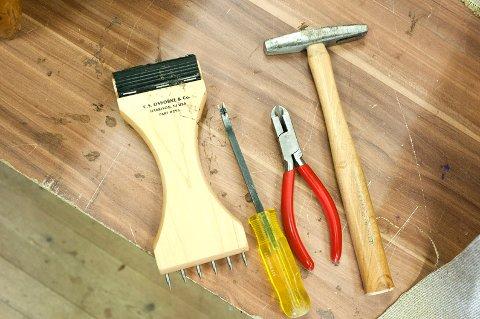 Møbeltapetsererverktøy: En gjortbåndstrammer, et verktøy til å lirke ut stifter, et verktøy til å dra ut stifter med og en magnethammer.