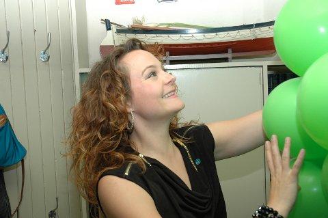 Rebekka Borsch henger opp grønne ballonger på Venstres valgvake.