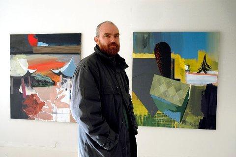 Arne Revheim foran to av de malerier som han stiller ut i Østfold Kunstnersenter. Begge maleriene er fullført den siste måneden.