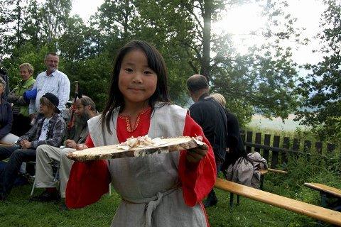 Hedda Rong Ek (6 1/2) viser fram flatbrød og røykt sik. Hun har gledet seg lenge til middelalderfesten og kjøpt en ny kjole til anledningen. foto: IDA thune øritsland