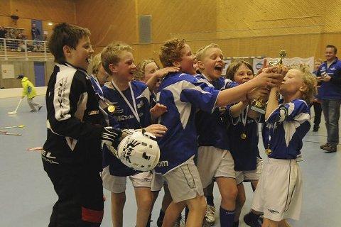 pokaljubel: Simen Aspeholen kysser pokalen, og blant gratulantene er blant annet Sindre Rafnung (f.v.), Henrik Gommerud og Andreas Sivertsen.