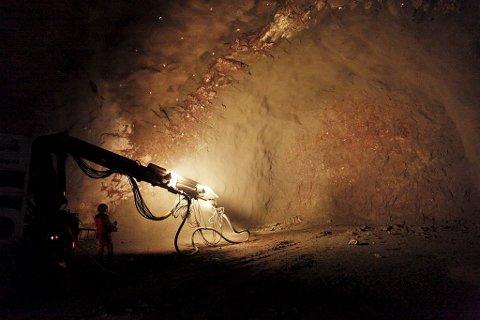 En operatør styrer hele arbeidet med å sprøyte taket i tunnelen med et åtte centimeter tykt lag betong iblandet glassfiber.
