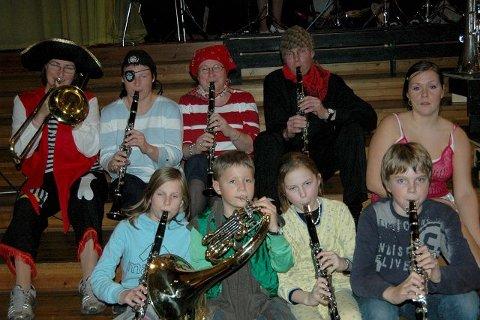 """Glade musikanter og sangere samlet på """"ett brett"""" i Symra kino. 1. rekke fra venstre: Julie Mikaelsen, Ole   Bendik Midtbust, Julie Kollandsrud og Geir Øvrebø, alle klarinett. Bakre rekke fra venstre: Eli Zahl, trombone, Carina Brobak, Tove Brekken og Morten Nystrøm, alle tre klarinett og Andrine Fendeland, barnekonsertens konferansier."""