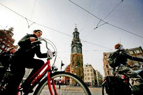 Pass deg for syklistene i Amsterdam. Eller du kan leie en sykkel og slå deg sammen med dem. Dette er fra det hektiske krysset ved tårnet Munttoren.