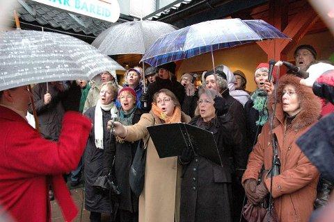 Nordstrand musikkselskap måtte beskytte seg med paraplyer i det kraftige regnet under julegrantenningen på Sæter.