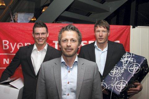 FEIRET: Kim Tajet Skaug (til venstre) ble årets nykommer, og Johnny Jensen (til høyre) årets spiller da Nøtterøy Håndball feiret sesongen med bankett på Quality Hotel Tønsberg lørdag kveld. Her poserer de to sammen med trener Geir Erlandsen.  Foto: Nøtterøy Håndball
