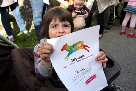 LIERDAGSKUNSTNER. I tillegg til å ha laget kunst til sin egen utstilling, hadde barna i Utsikten barnehage vært med på å dekorere en av Lierdagssauene. Her viser Daniel Vonheim (2 1/2) fram diplomet han fikk for innsatsen.
