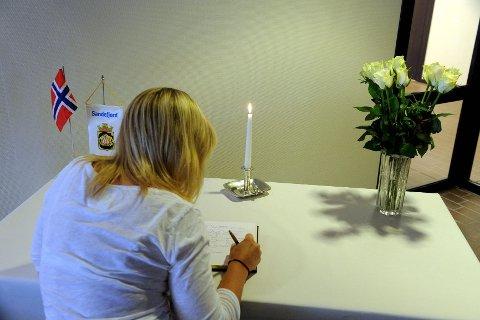 Det er satt opp et bord og en stol der kondolanseprotokollen ligger. Det er også tent et lys og satt ut blomster.  Foto: Per Langevei
