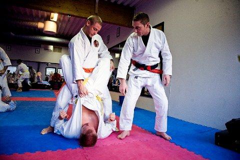 Instruktør Bryan Morris instruerer Marius Stene(stående) i riktig grep på Michael Johnsen