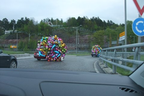 To biler rullet gjennom Kjellekrysset på 17. mai. Overlesset med heliumballonger.