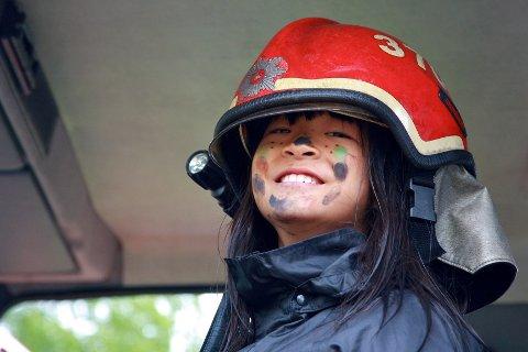 Linnea Nesset (11) fra Lierbyen fikk prøvesitte en ekte brannbil - med brannhjelm på hodet.