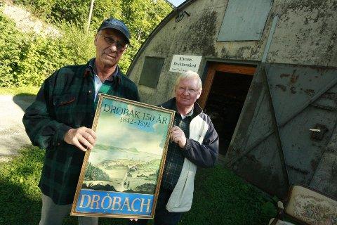 Willy Ruud og Tom Gaardsø er glade for at mange av de som tar turen innom bruktmarkedet er like mye opptatt av gjenbruk som å finne de skjulte skattene. Her poserer de med plakaten fra byjubileumet i 1992.