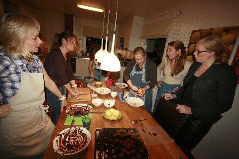 Lise Sæther skreller det gule av appelsinene mens det diskuteres hva som gjenstår før tapasene kan settes på bordet.