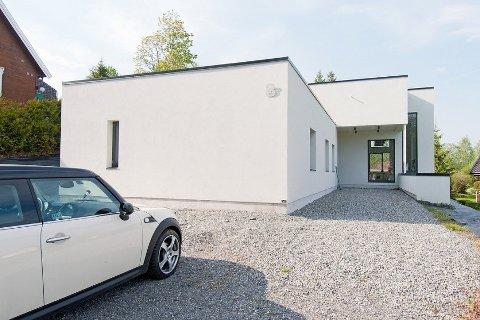 Gårdsplass, fasade og inngangsparti i lysmalt betong.