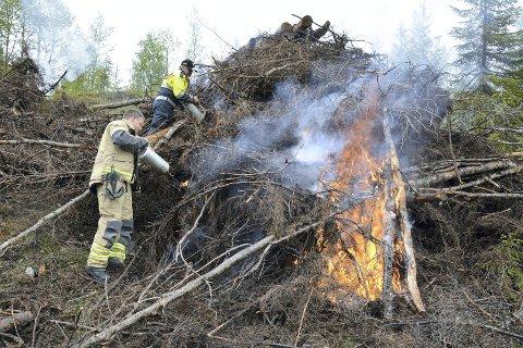 Fyrte: Det tok sin tid før man klarte å få det til å brenne skikkelig i denne haugen, som så igjen skulle slukkes. Men til slutt lyktes det og vannslangene kunne skrus på. Foto: Ivar Bae