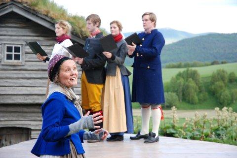 Ingunn Løvold er i storform når hun forteller historien om haugianerkvinnen Sara Oust fra Vingelen. Med seg har hun fire sangere (bak fra venstre): Rønnaug Tingelstad, Lars Tingelstad, Kjersti Tingelstad og Andreas Moen. Sammen skaper de tidsbilder og tablåer som illuderer hvordan livet til Sara kan ha fortonet seg for 200 år siden. Syngespelet «Noen må gå foran» settes opp på Oustatunet i Vingelen, der Sara ble født. Med bygda Vingelen som naturlig bakteppe og med stemmeprakten til de fire sangerne tas publikum rett med inn i en annen tid, og Sara blir levende. Alle foto: Karin Tørklep Sletten