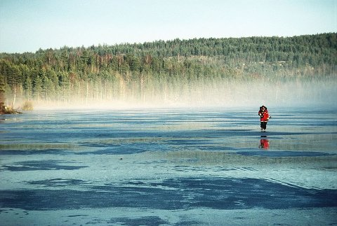 """Rolf Utgård er en ivrig turskøyteløper og fotograf. Bildet av isfiskeren som skøyter mot demningen ved Rustadsaga er fra hans egen bok """"På skøyter i marka""""."""