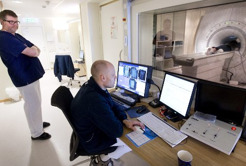 UNDER HUDEN: Instituttsjef Gary Haraldsen følger med mens radiograf Arne-Idar Johansen, MR-ansvarlig ved Unilabs Røntgen Ski, undersøker en pasient. FOTO: BJØRN V. SANDNESS